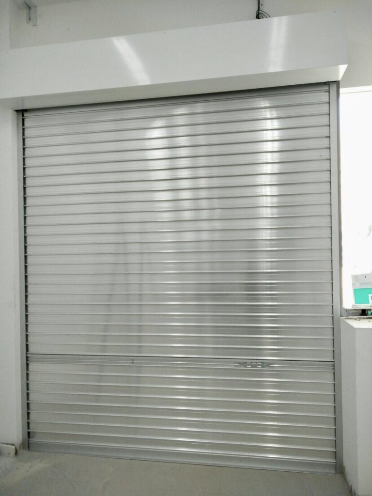 Manually Operated Aluminium Roller Shutters for Retail Shop at Geylang Road. Lockset Adjusted More Towards Right Side Due to Fixed Glass Panel in front of the Roller Shutters